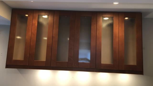 Kansas City, MO - Decorative glass panels in cabinets look beautiful and hide the mess.  Add lighting for even more ambiance.