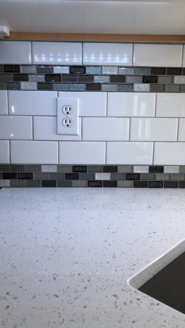 The design in this kitchen is subway tile with a mosaic tile inlay.