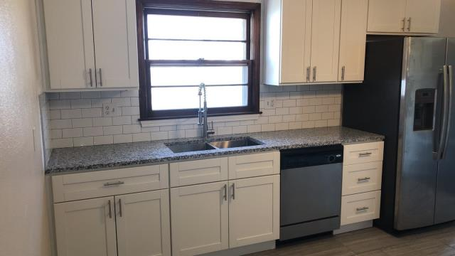 This kitchen remodel has a subway tile backsplash and a pull down kitchen faucet.