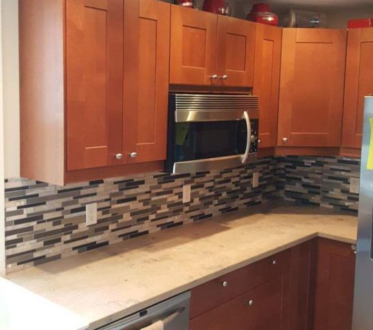 Using a glass tile back splash adds elegance to this kitchen.
