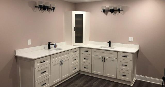 This bathroom remodel features an L shape corner vanity with a double sinks.