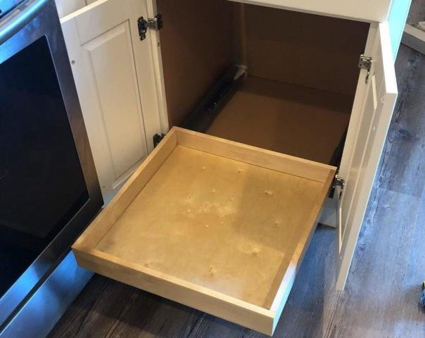Raytown, MO - Installing roll out trays in your kitchen cabinets allows easy access to the items you store there.
