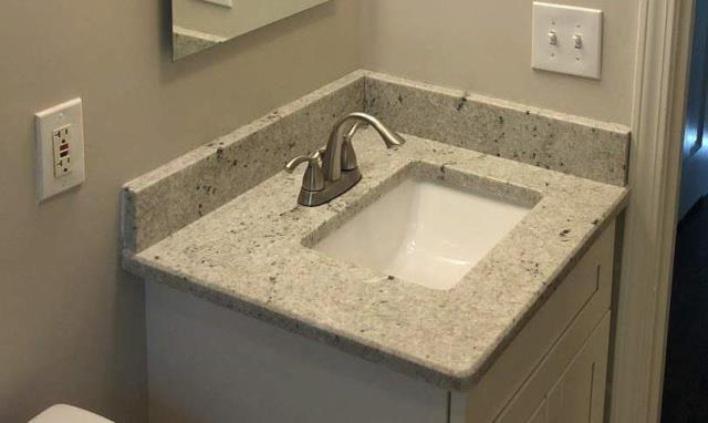 This is a colonial white, granite countertop from Legendary Stone installed in this bathroom.