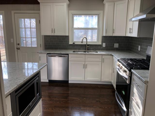 Amazing kitchen renovation with white shaker cabinets, stainless steel appliances, and grey glass subway tile backsplash.