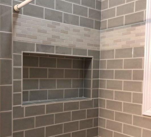 Setting the inlay tile above mid-line gives this shower a unique look.  Built in shampoo caddies add design and function.