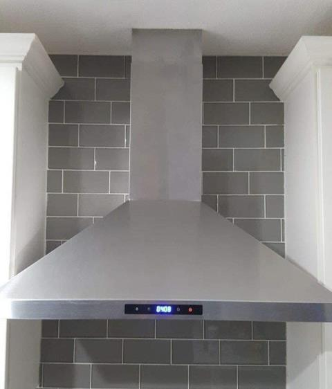 This kitchen remodel includes a wall mounted range hood and full wall, grey subway tile backsplash.