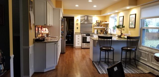 "New white Shaker cabinets, real hardwood floors, soffit removal for an open feel & look, Santa Cecelia countertops, 4"" & 6"" recessed fixtures for plenty of light, custom stainless steel backsplash behind new chimney style vented range hood, oversized snack bar for plenty of legroom."