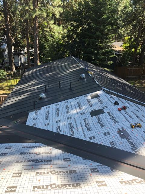 Bend, OR - Finishing a black standing seam metal roof installation in Deschutes River Woods.