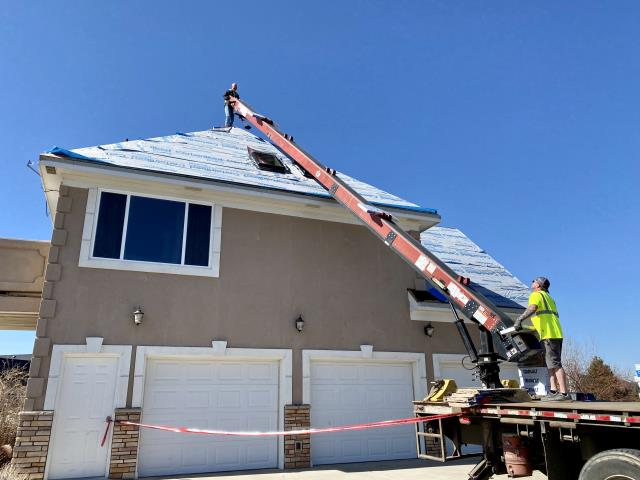 Berthoud, CO - Beacon Roofing Supply can be seen here loading this roof in Berthoud for us with CertainTeed Northgate Class IV Impact Resistant Shingles in the color Heather Blend.