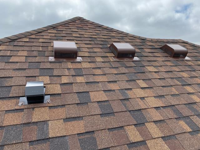 Longmont, CO - We prefer to install ridge vent to ventilate most attics - ridge vent allows more air to escape the attic than slant back vents do, which are shown here.  There are roofs that do not have a lot of ridge line, so they are not conducive to having ridge vent installed.  You can see on this roof in Longmont that we added some slant back vents to increase the attic ventilation because there was very little ridge on this roof.  The shingles on this roof are Certainteed Northgate Class IV Impact Resistant Shingles in the color Burnt Sienna.