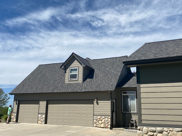 Longmont, CO - This homeowner in Longmont is taking a look at his new CertainTeed Northgate Class IV Impact Resistant roof that we installed.  They are ready for the next summer storm.  The shingle color on this home is Driftwood.