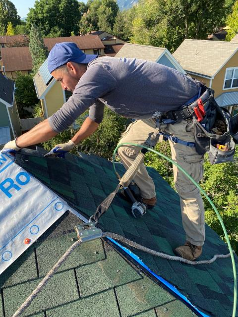 Boulder, CO - Gustavo up on the peak of a steep roof the crew was working on this week in Boulder.  The shingle he is installing are CertainTeed Northgate Class IV Impact Resistant Shingles in the color Hunter Green.