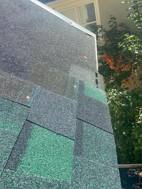 Boulder, CO - This picture of a roof we just did in Boulder shows a great example of the components of a roof installation. We installed water and ice shield on the eaves and new edge metal on the rake and eave.  The water and ice goes under the rake edge metal and over the eave metal.  Then you can see a bit of the starter strip and then the shingles going on.  The shingles being installed are CertainTeed Northgate Class IV Impact Resistant Shingles in the color Hunter Green.