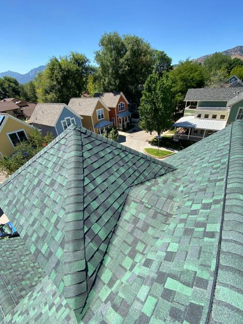 Boulder, CO - This roof in Boulder was steep and complicated, but the crew did an amazing job on it.  Here you see a cricket.  You normally see them behind chimneys, but this one is sandwiched in behind that peak you see.  It will make sure snow and water do not build up behind that peak.  The shingles shown here are CertainTeed Northgate Class IV Impact Resistant shingles in the color Hunter Green.