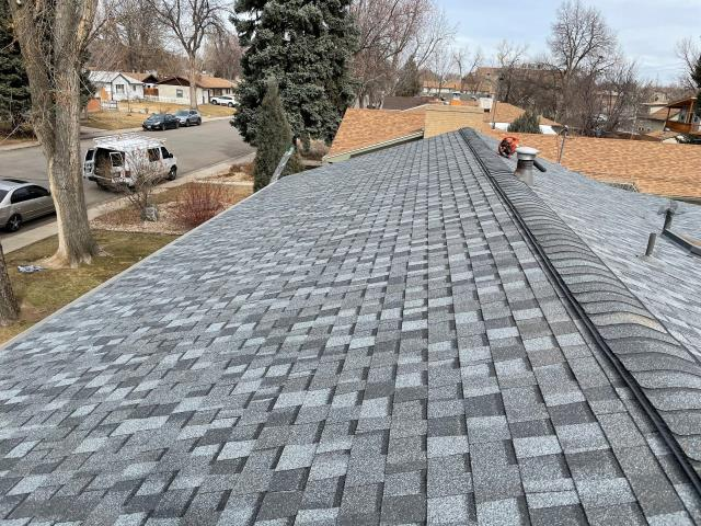 Longmont, CO - The crew is cleaning up and putting the finishing touches on this roof in Longmont.  The shingles we installed are CertainTeed Northgate Class IV Impact Resistant shingles in the color Pewter.
