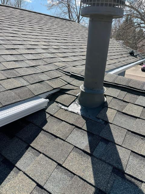 Longmont, CO - There is a lot going on in this one small area of this roof in Longmont - ridge line, ridge vent, heater vent pipe, two roof areas meeting, gutters, etc.  The shingles we installed here are CertainTeed Northgate Class IV Impact Resistant Shingles in the color Weathered Wood.