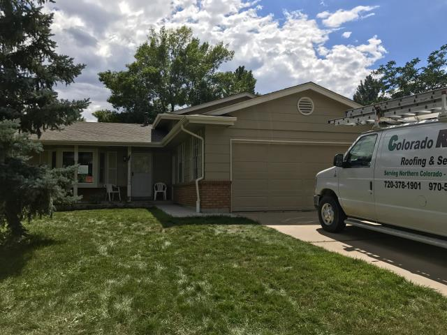 Broomfield, CO - You can see in this picture of a home that we just re-roofed in Broomfield, that the crew was there and just finishing up their work and clean up when I stopped by to take the picture.  This home is a rental that we re-roofed for the homeowner.  The color of the shingles that the homeowner chose is Weathered Wood.  The shingles that we installed were GAF Timberline HD shingles.