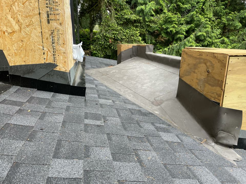 Kirkland, WA - New construction 60mil TPO in dark bronze transition to GAF Timberline HDZ roofing shingle in charcoal.