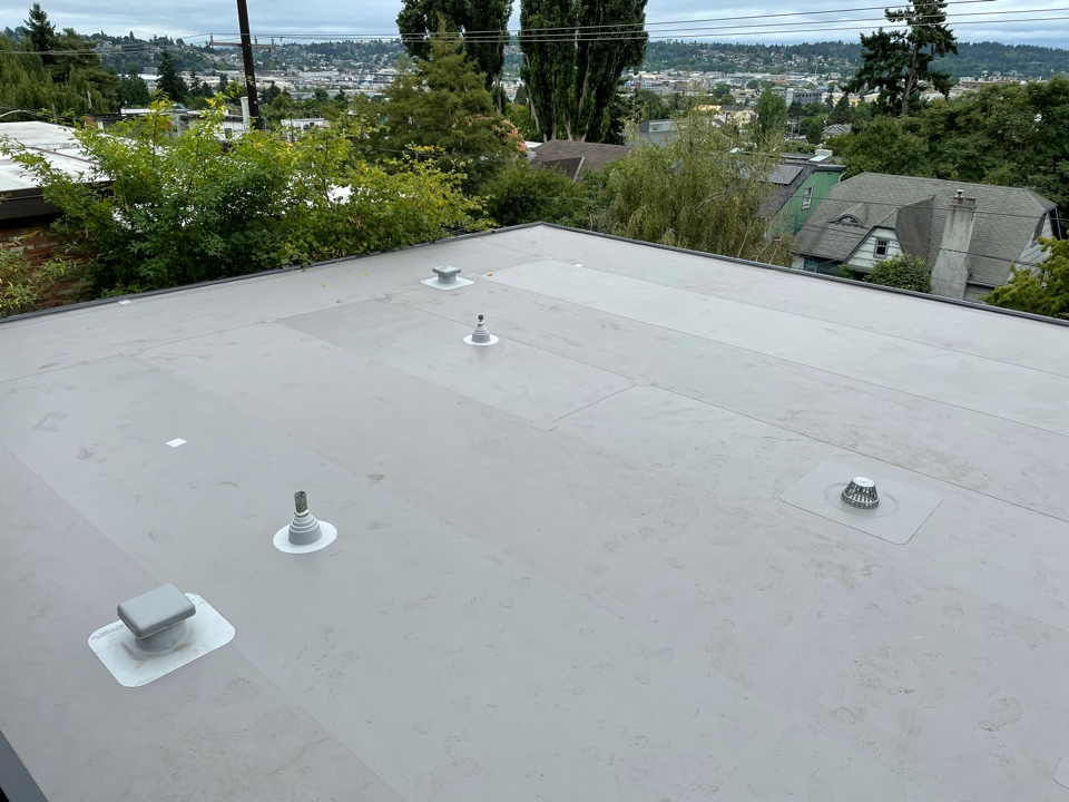 Seattle, WA - Apartment building re-roof with tear off of 3 layers of existing roofing, new mid roof drains, and installation of Firestone 60mil TPO membrane roofing in gray.