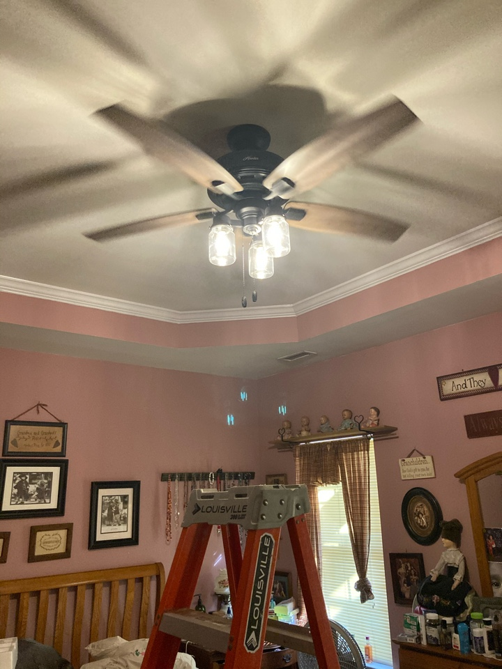 Electrician in Clayton installing fan in master bedroom and a light fixture in bathroom