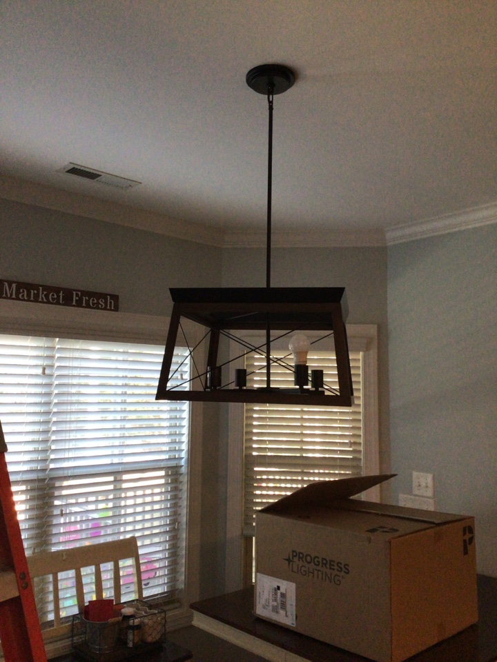 Electrician in Clayton installing chandelier in the dining room