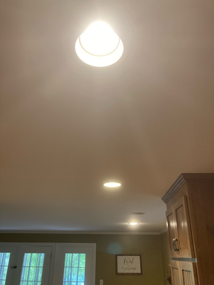 Electrician replacing recessed lights in kitchen