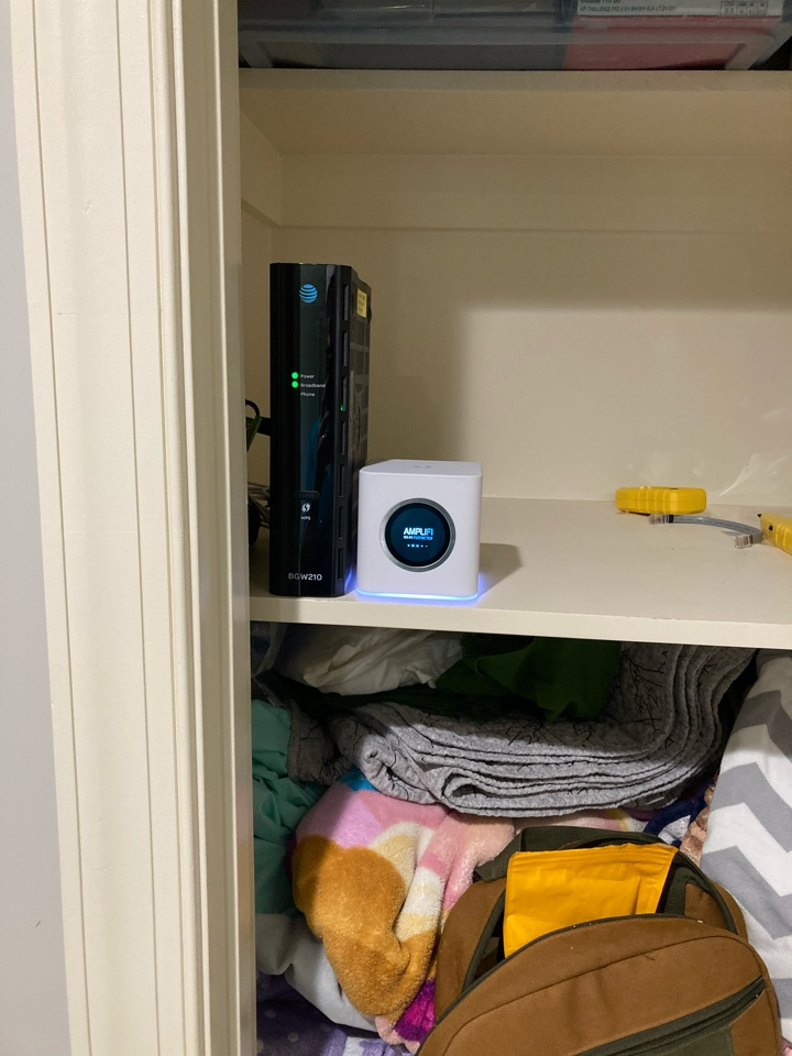Electrician moving internet modem and setting up WiFi hub in a home