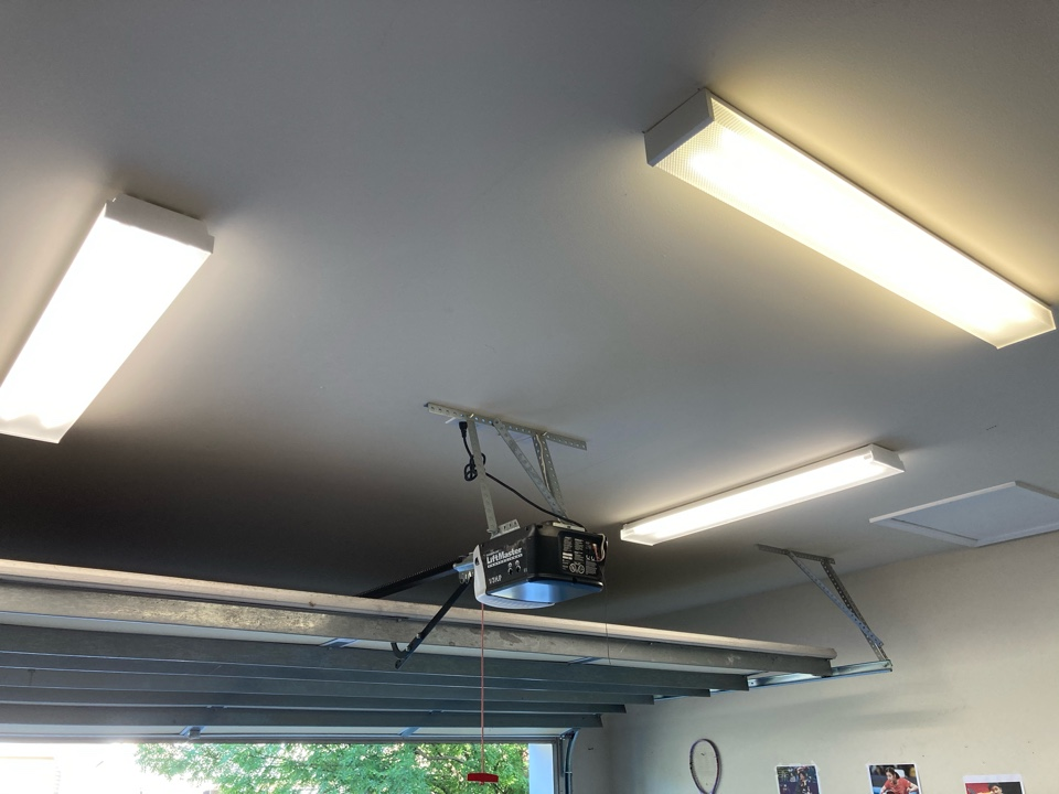 Electrician installing two new LED fixtures in a garage