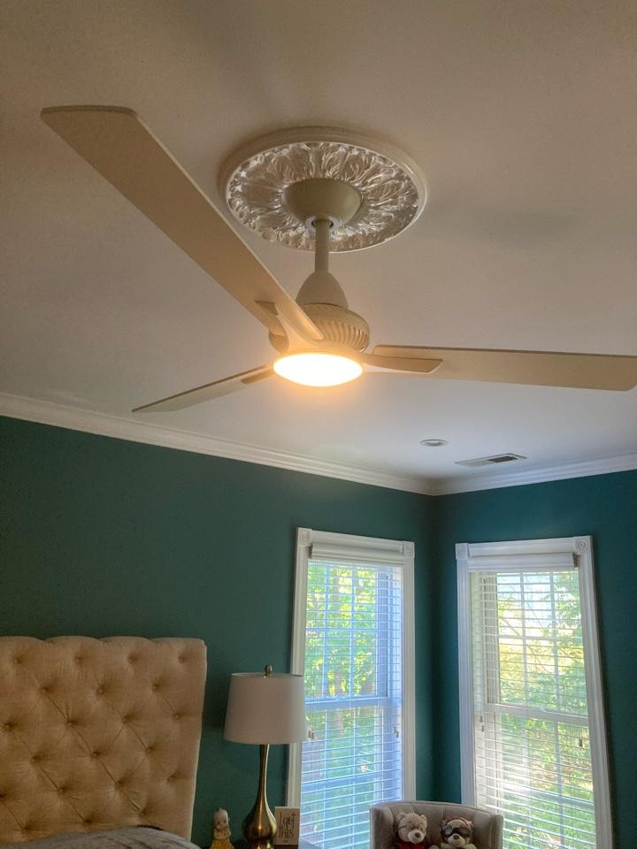 Electrician installing new ceiling fan in a bedroom.