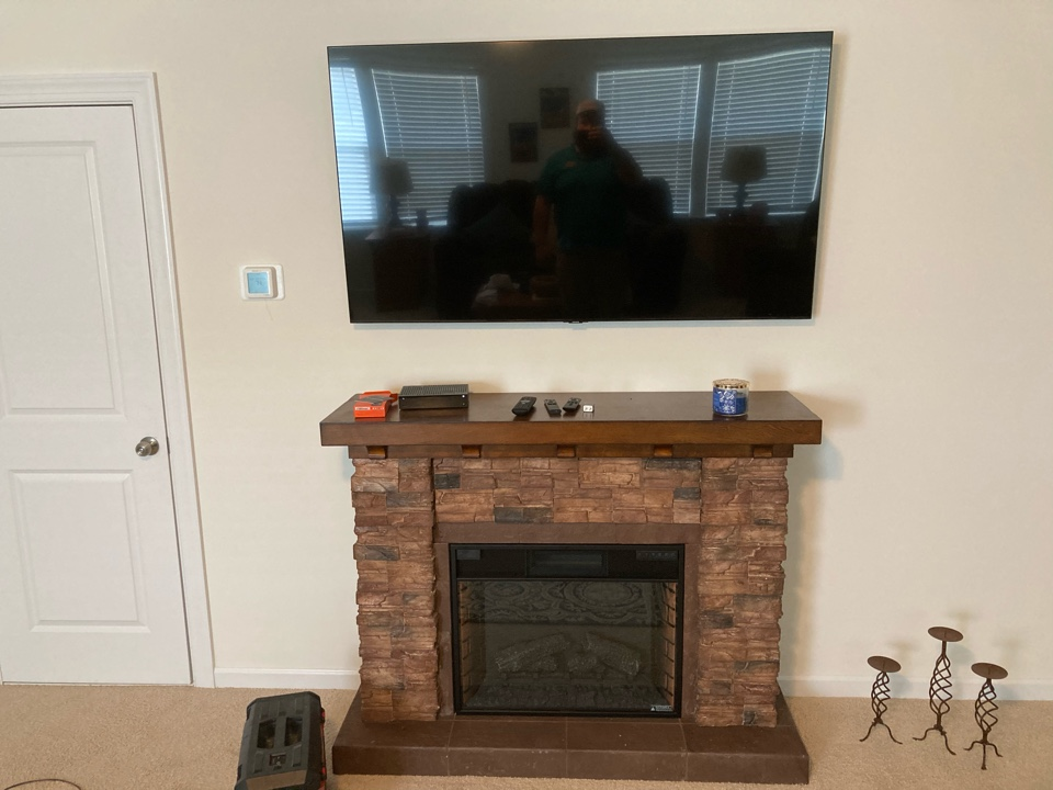 Electrician mounting and running power and internet to a new tv.