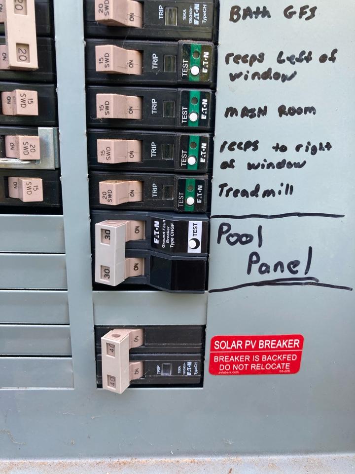 Electrician replacing a faulty pool pump breaker.