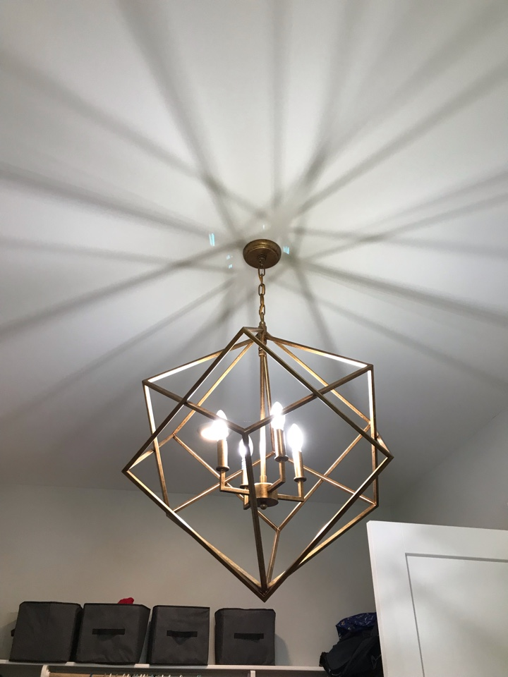 Electrician installing ceiling fan in exercise room and installing chandelier.