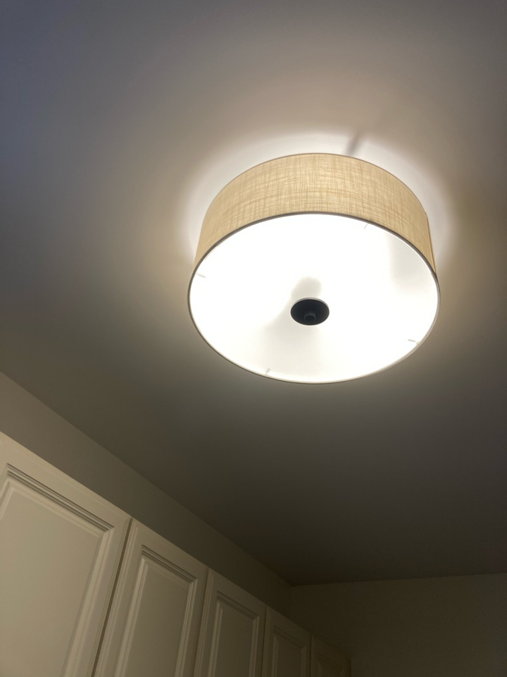 Electrician installing a light fixture in a laundry room.