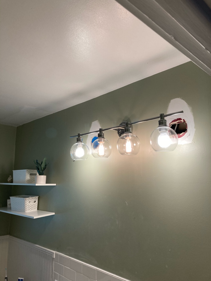 Electrician installing a new vanity light in a bathroom.