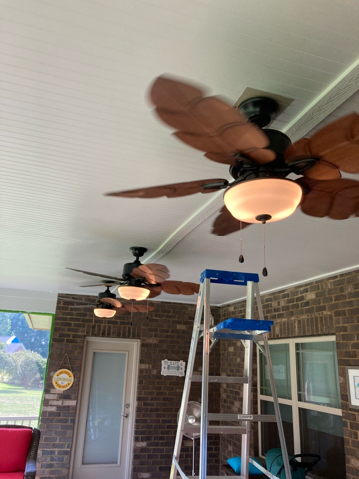 Electrician installing three ceiling fans on a back porch.