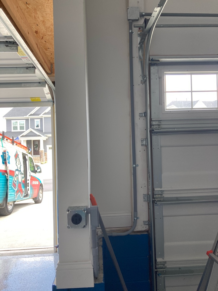 Electrician installing a new Tesla charger receptacle in a garage