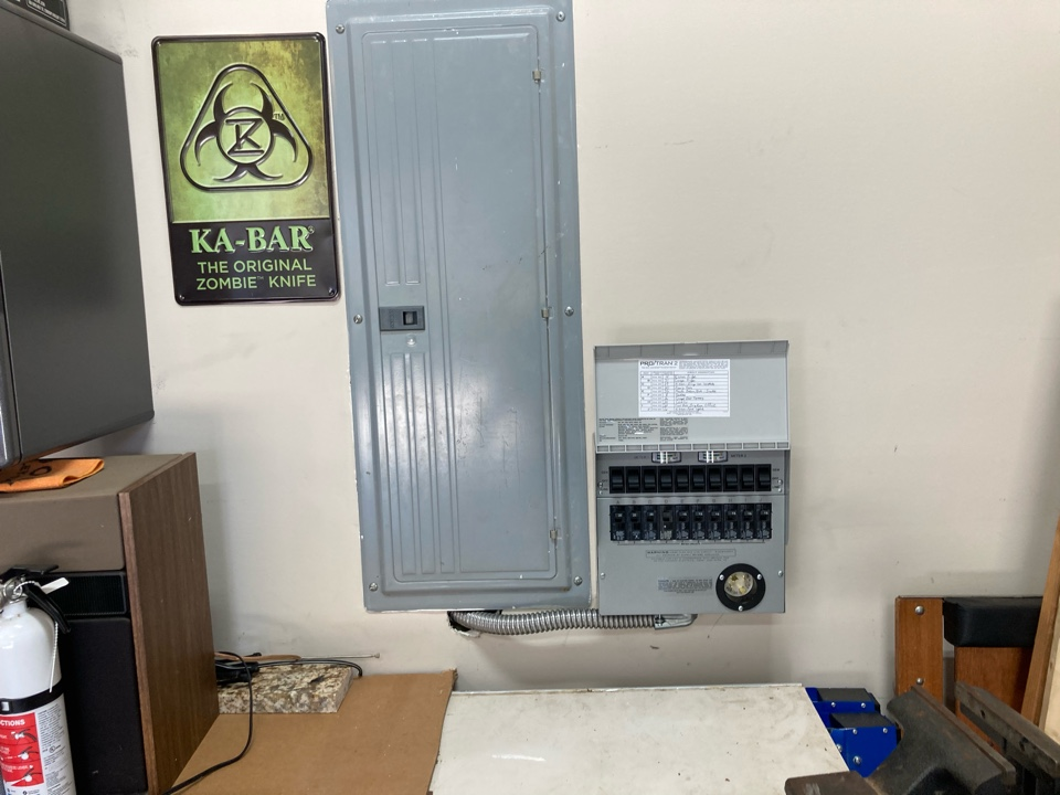 Electrician installing a portable generator transfer switch for convenience and comfort during a power outage.