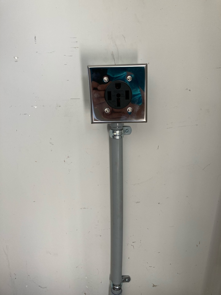 Electrician installing a Tesla charging receptacle in a garage