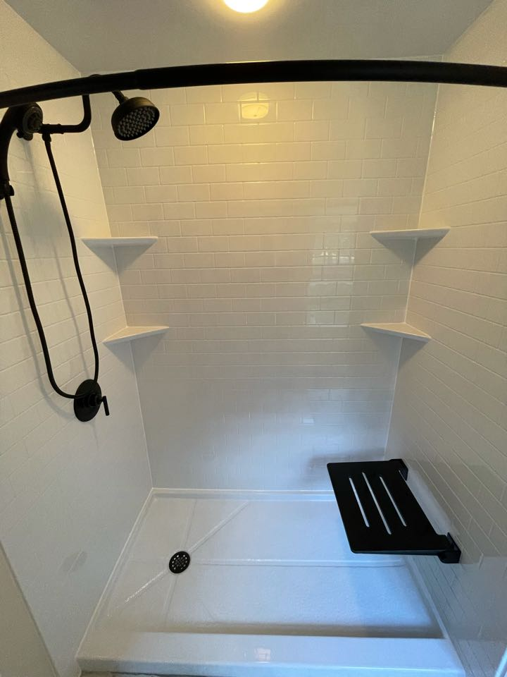 Norwell, MA - Installed a stand up shower in place of old bathtub . Black finish with the subway walls look amazing! Updated all the plumbing with moen fixtures and free standing shower bench .