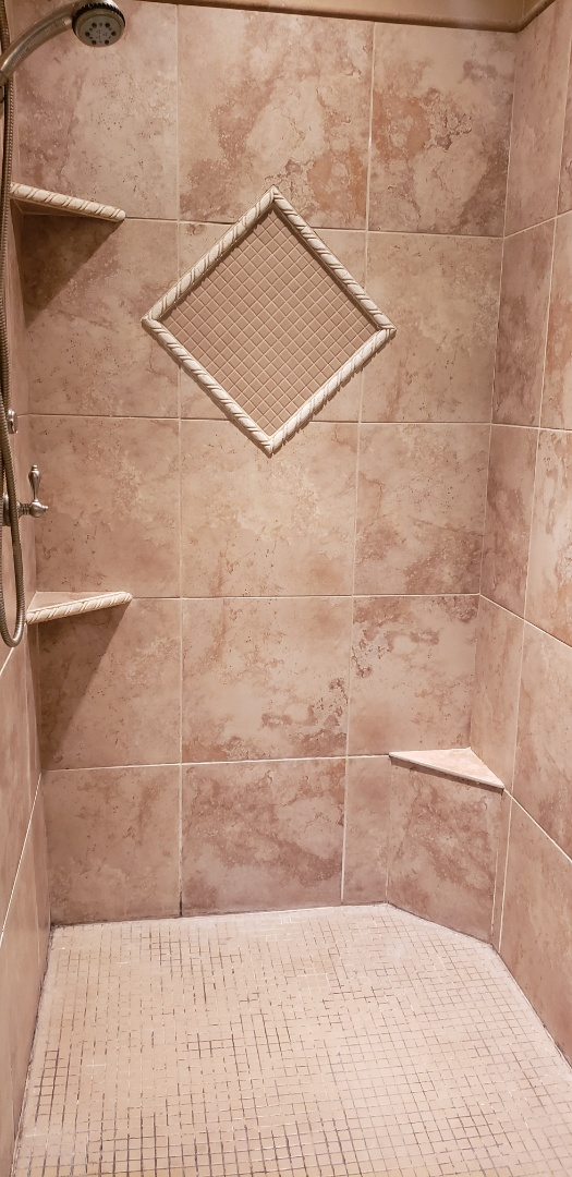 Tiles shower base and onyx walls.  New oil rubbed bronze fixture and shower door