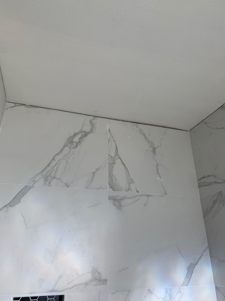 Marble looking porcelain tiled shower. With custom shower box and glass doors.
