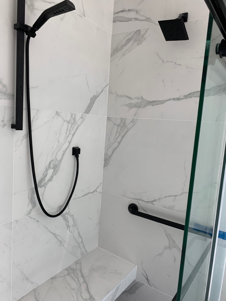 Shower remodel to remove existing fiberglass tub shower and replace with walk in tile shower with bench and ADA grab bar in matte black.