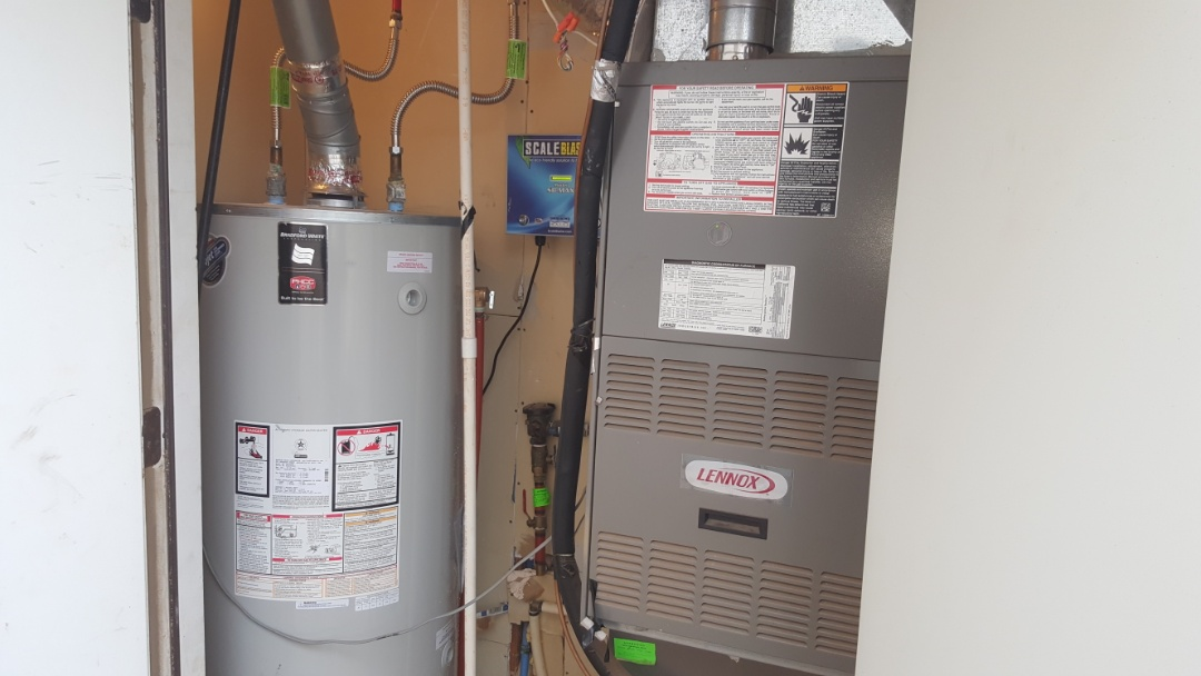 Edmond, OK - Installing new 75 gallon water heater natural gas install two new flexible water heater connectors to cold water valve and hot water PEX piping on plumbing system for residential home in Rose Creek addition also straightened out drain pan for water heater during service