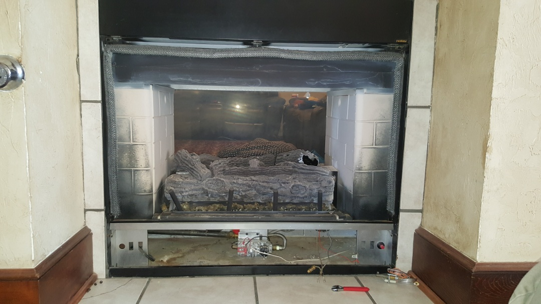 Edmond, OK - Doing gas fireplace repair on Heatilator gas fireplace after client bronze option repair of gas fireplace insert after doing renovations on the ignition and safety system also cleaned the glass to get the white residue off of the glass of the fireplace as well as put a Polish on the cabinet of the gas fireplace to restore it to clean condition