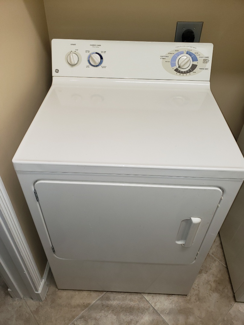 THE TECHNICIAN IS REPAIRING A GENERAL ELECTRIC DRYER.