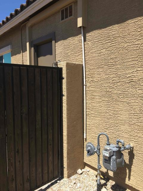 Goodyear, AZ - In Goodyear, near West Verdin Road and West Westar Drive returning to secure drain line that had detached from side of house. Installed anchor on one hole strap to insure that it does not come loose.