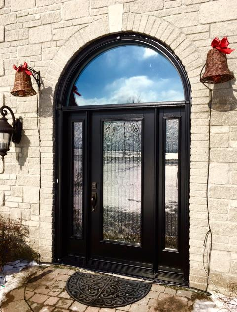 Goulbourn, ON - Wow! This beautiful wood-hybrid custom made door combines the elegance of wood with the durability of steel. The door and sidelites feature a forged iron grill design and the clear glass transom above maximizes light.