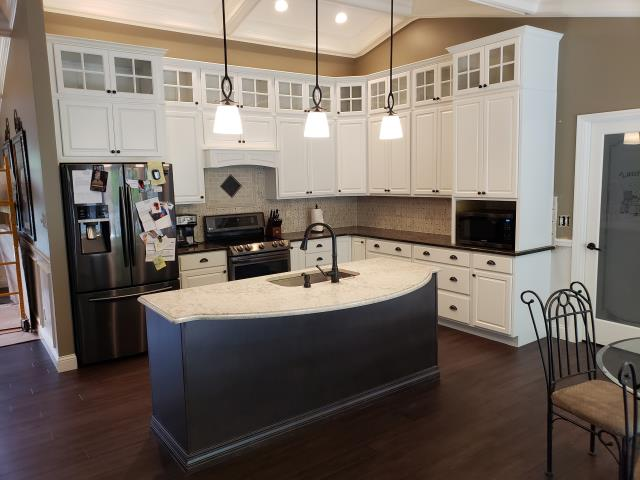 St. Louis, MO - Latest stunning new kitchen by designers, Bill Lucas and Marc Fisher in Oakville, MO!  Stacked white cabinets, pendant lights, granite island, engineered hardwood flooring, oil-rubbed bronze fixtures ... Wow factors all around!