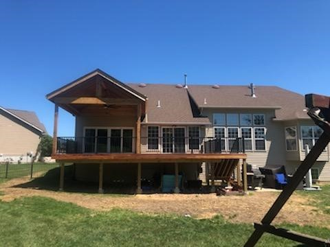 Saint Charles, MO - Talk about expanding one's living space!  WOW!  New Tigerwood deck with black aluminum handrails.  We added a roof made out of Tigerwood with a fan for increased comfort and we converted three windows into 2 sliders maximizing their view.