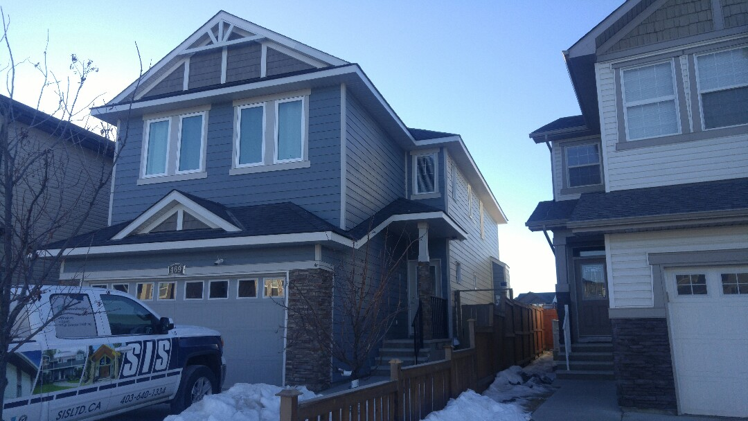 Calgary, AB - Previous hail damaged vinyl siding, re wrapped with Boothbay Blue Hardie Plank and Cobblestone Hardie Trim Accents